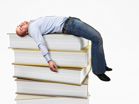 tired worker: portrait of stressed man sleeping on a 3d book pile
