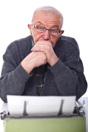 portrait of senior man with aged typewriter isolated on white photo