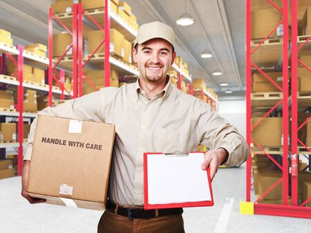 smiling caucasian delivery man and 3d warehouse background photo