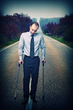 young businessman with crutch and long way background photo