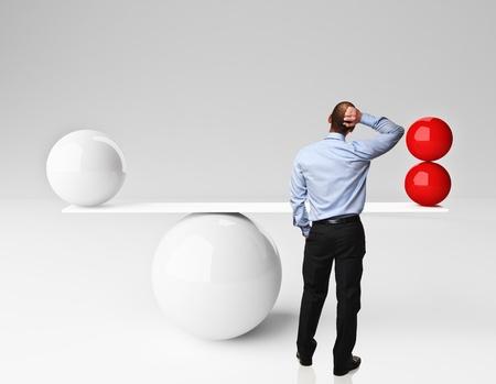 compare: thinking caucasian man and 3d balanced balls