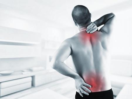 dolor de espalda: hombre en casa con dolor de espalda en la zona roja