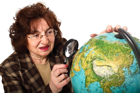 senior teacher holding magnifier and looking the world map Stock Photo - 8815354