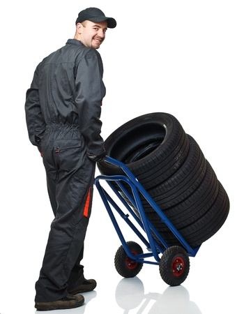 manual worker with handtruck and tires on white background photo