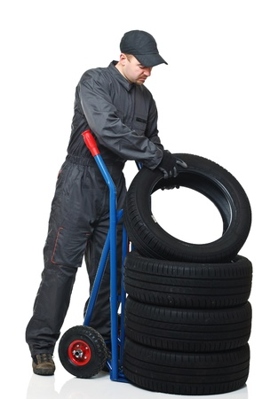 caucasian mechanic pose tire on handtruc isolated on white background Stock Photo - 8815397