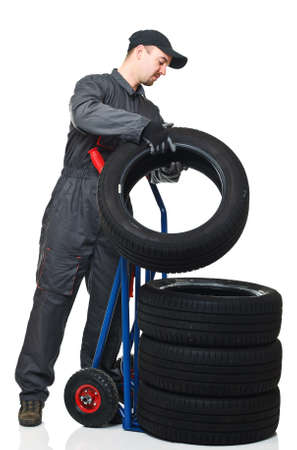 caucasian mechanic pose tire on handtruc isolated on white background Stock Photo - 8815405