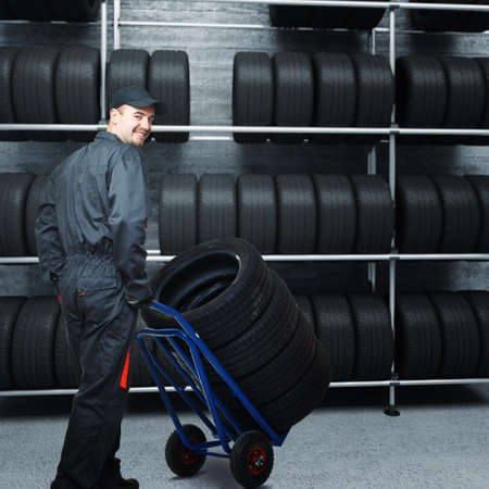 caucasian mechanic at work with tires and 3d garage background Stock Photo - 8943883