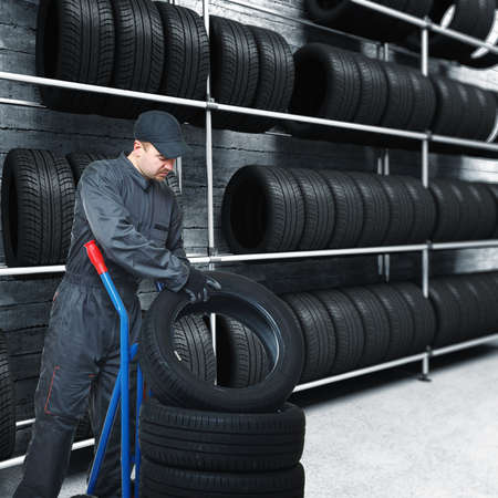 caucasian mechanic pose tire on handtruck and 3d garage background Stock Photo - 8943888