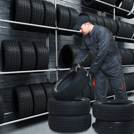 garage: caucasian mechanic at work with tires and 3d garage background