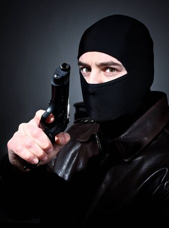 balaclava: fine closeup portrait of criminal holding pistol Stock Photo