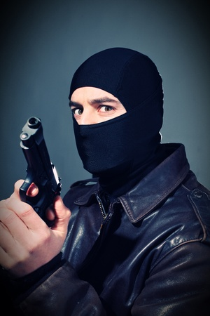 fine closeup portrait of criminal holding pistol Reklamní fotografie