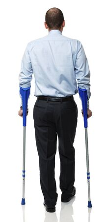 standing caucasian man with crutch isolated on white photo