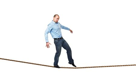 try: young businessman try to walk on rope Stock Photo