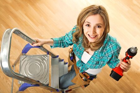 drill floor: smiling young woman with drill and wood floor background Stock Photo