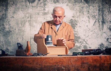 craftman: man at work with electric grinder on wood furniture part