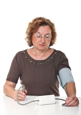 high blood pressure: senior woman check her blodd pressure with machine