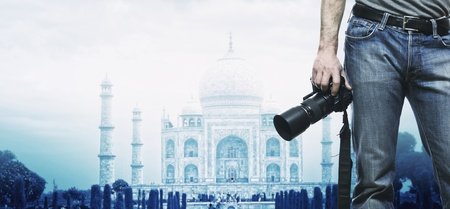 man holdin camera and  taj mahal background photo