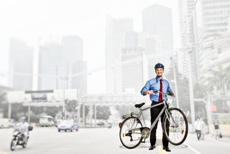 smiling caucasian businessman with his bike photo