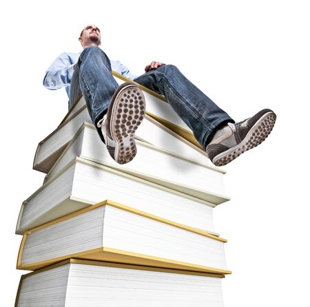 caucasian man sit on huge book pile photo