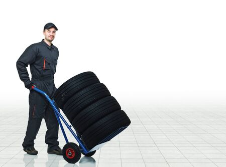 young manual worker with tyres Stock Photo - 11978732