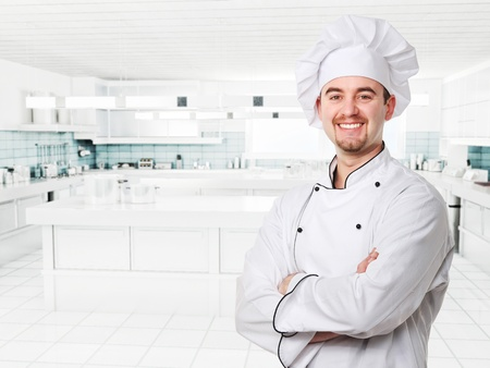 inox: smiling young chef in modern kitchen