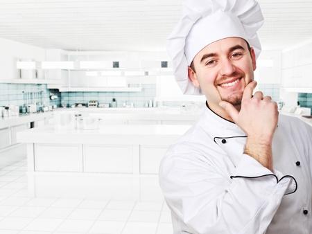 cocinero: sonriente joven chef en la cocina moderna Foto de archivo