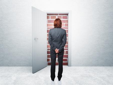staande vrouw en gesloten deur Stockfoto