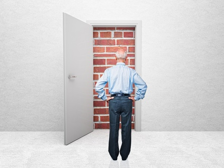 standing old man and door with brick wall Stock Photo - 12381492