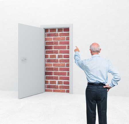 closed door: standing old man and door with brick wall Stock Photo
