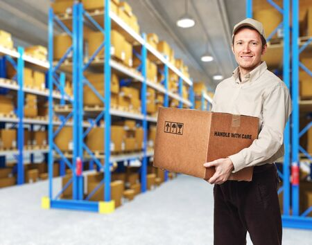 smiling delivery man in warehouse Stock Photo - 12381390