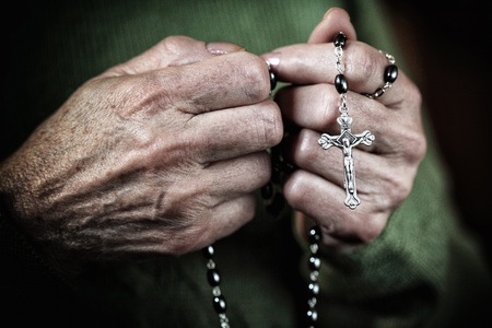 hands with classic catholic rosary photo