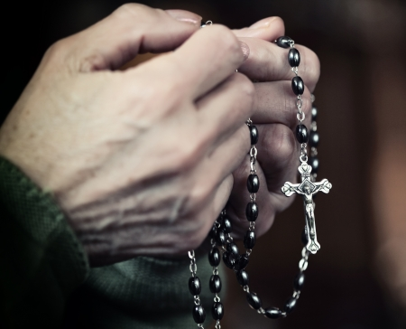 catholic: closeup on female hands with classic rosary Stock Photo