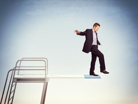 afraid: young caucasian businessman on springboard