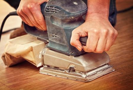 closeup on carpenter use classic sander