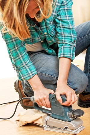 woman use electric sander on wood floor photo