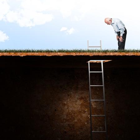 지하에: 노인은 땅 구멍 보면 스톡 사진