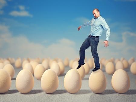 cautious: caucasian man walk on 3d eggs