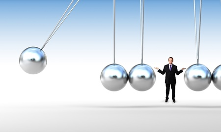 sphere standing: smiling businessman and classic newton cradle Stock Photo