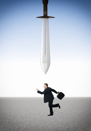 running businessman and damocles sword photo