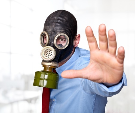 businessman with gas mask in office photo