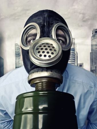 radiation pollution: businessman with gas mask and town background Stock Photo