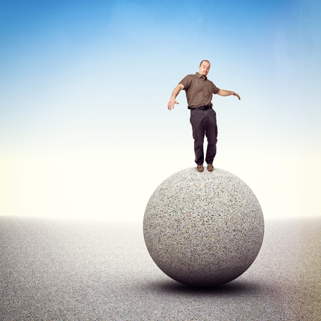 proble: man try to balance himself isolated on big rock sphere Stock Photo