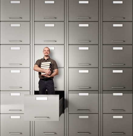 man with book in file cabinet drawer photo