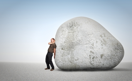 try: man try to move an huge stone Stock Photo