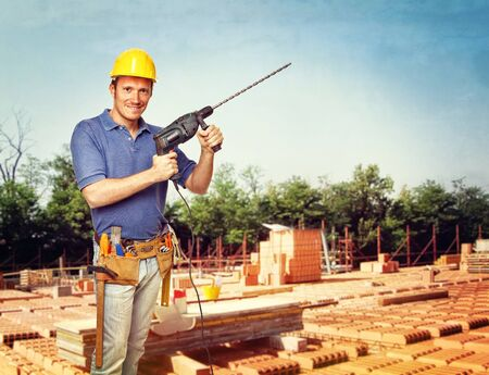handyman with drill in construction site photo