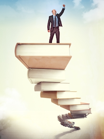 improve: happy businessman on books stair Stock Photo