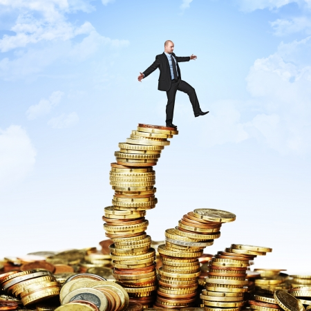 rich: man try to balance himself on coin piles Stock Photo