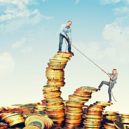 pulling money: business team on euro coin piles Stock Photo