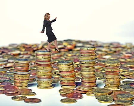 businesswoman walk on euro coin piles photo