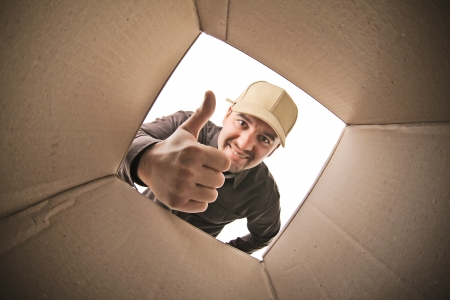 smiling delivery man view fron parcel inside photo